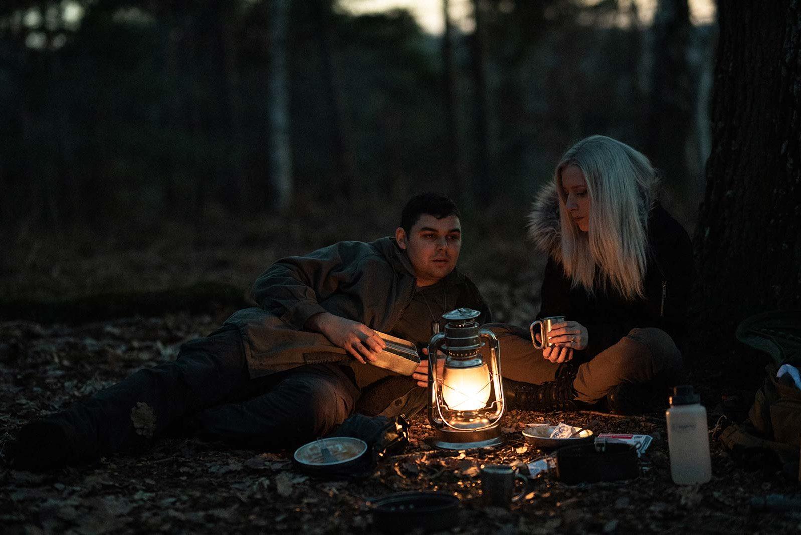 Couple qui mange à la tombée de la nuit lors d'un bivouac.