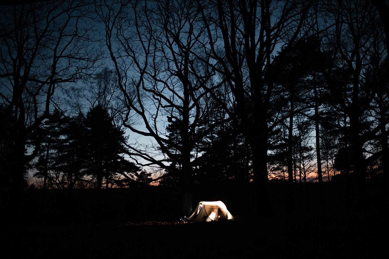 Tente illuminée au milieu de la nature de nuit.