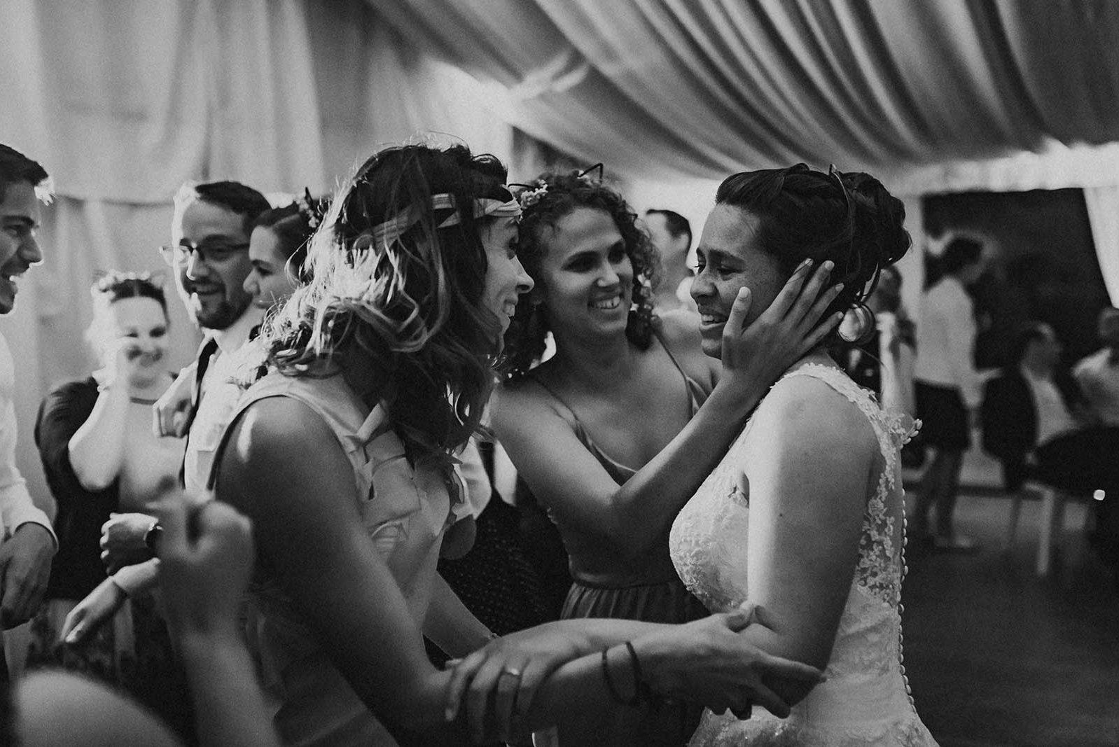 Des convives câlinent la mariée lors de la soirée.