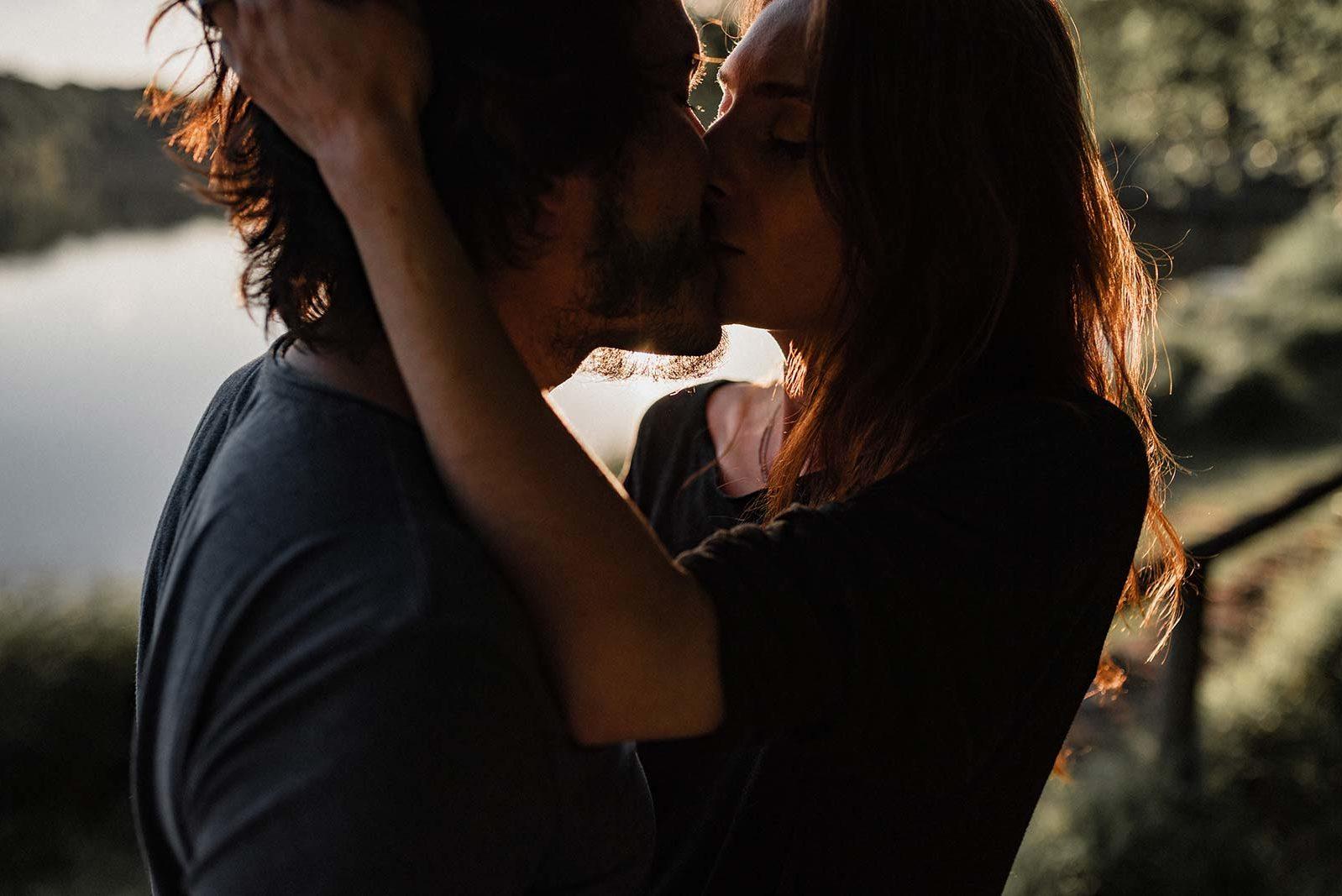 Couple qui s'embrasse au bord d'un lac.