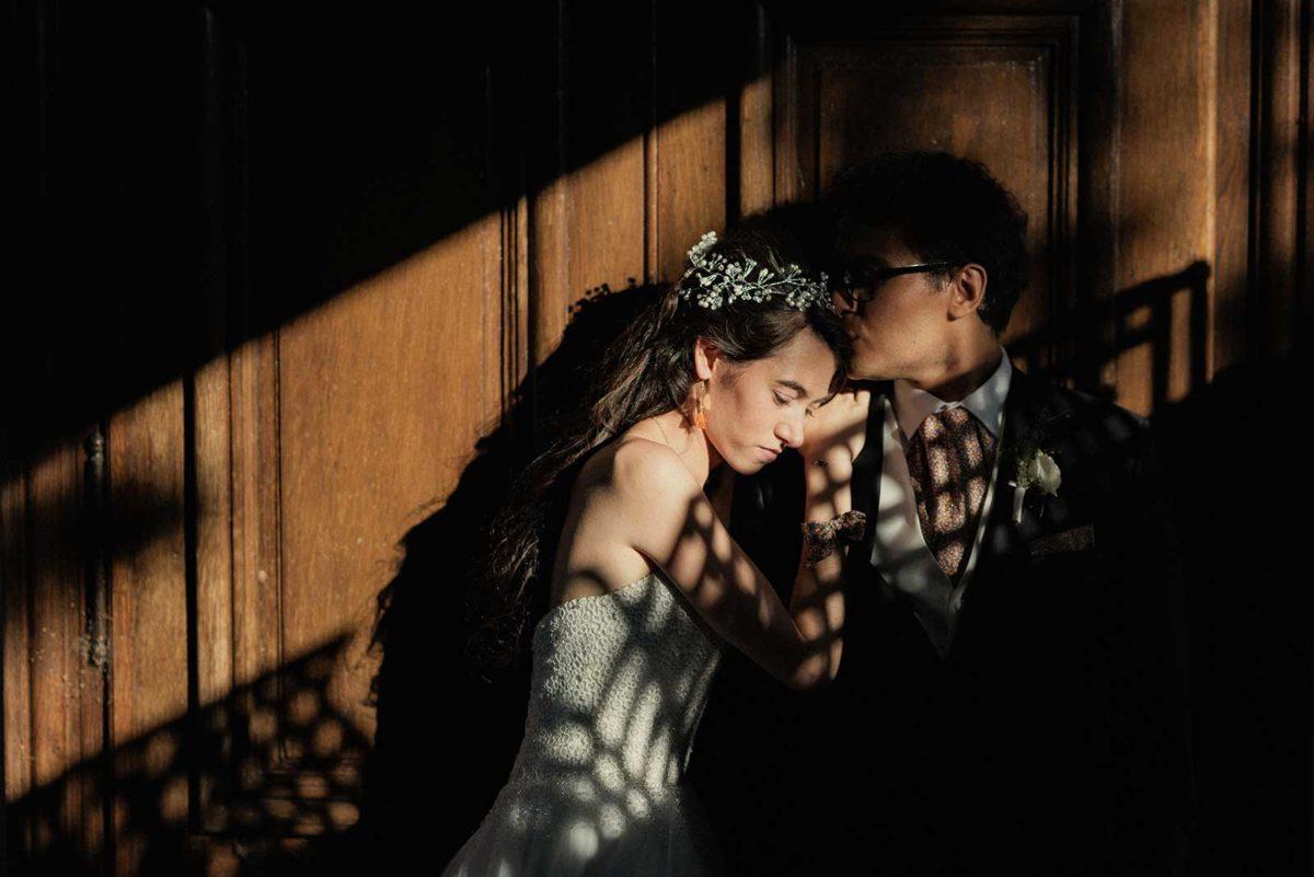 Couple dans un rayon de lumière contre une porte.