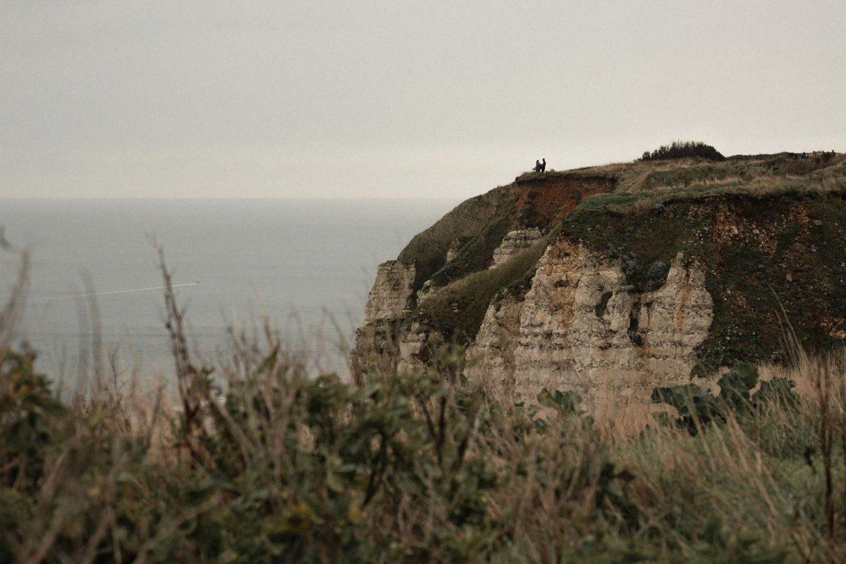 Couple au loin au bord d'une falaise en bord de mer.